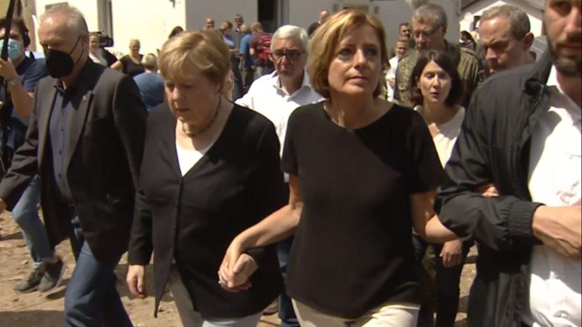 El gesto viral de Ángela Merkel. Tomó de la mano a su rival del SPD - que tiene esclerosis múltiple - para ayudarla a recorrer las zonas arrasadas por la inundación (Foto: AP)