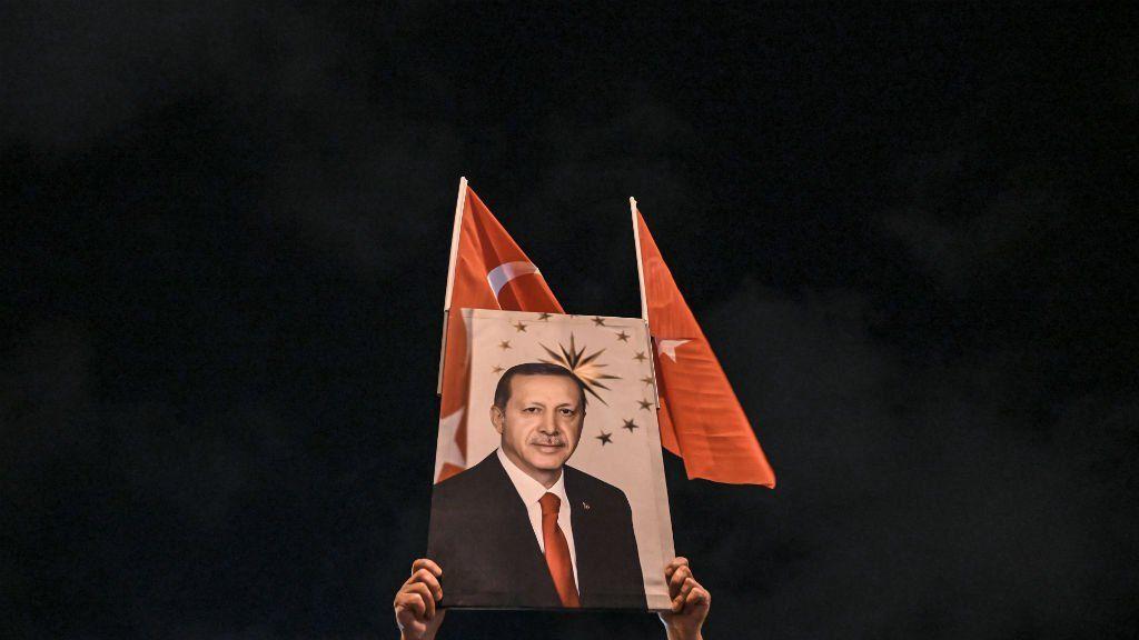 Un simpatizante alza una foto del presidente de Turquía Erdogan. El mandatario echó al titular del banco central turco Agbal por subir la tasa de interés. (Foto: AP)