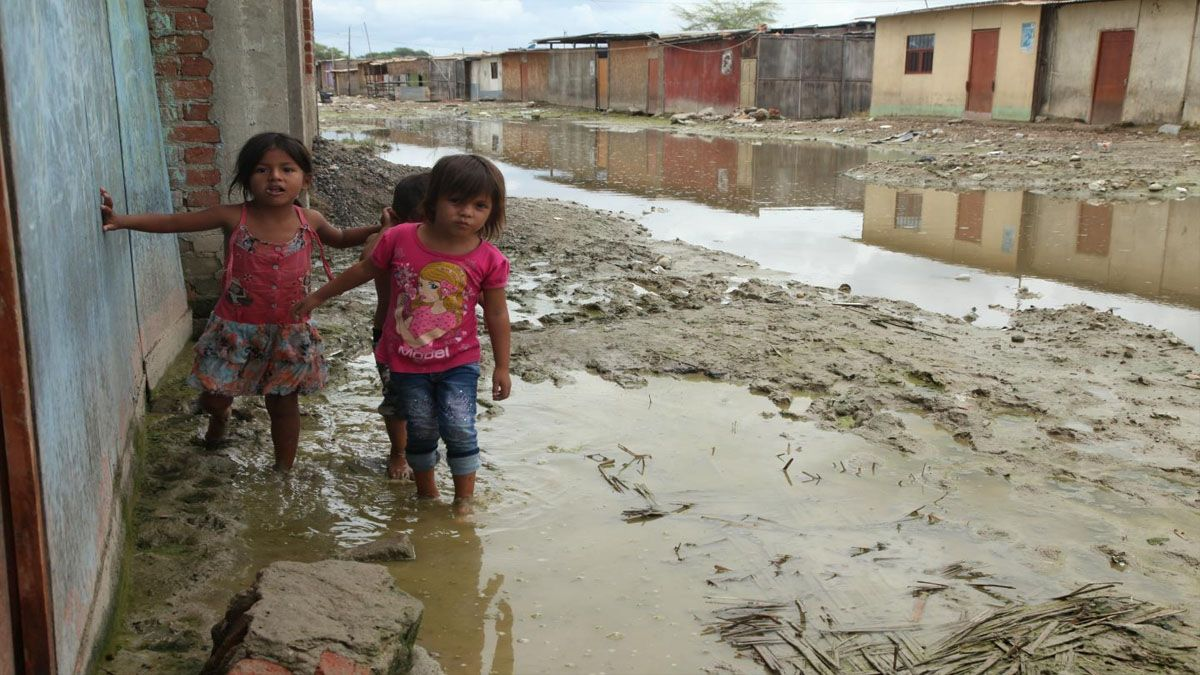 Niños se desplazan en un deprimido suburbio peruano luego de una intensa lluvia. Centenares de millones de niños y niñas en todo el planeta viven bajo la amenaza de inundaciones, entre otras calamidades asociadas al cambio climático. (Foto: Unicef)