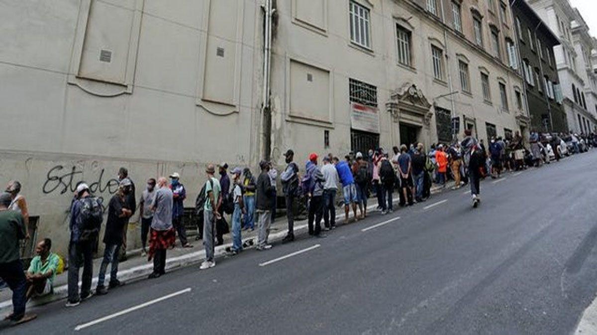Una larga fila de gente espera a recibir alimentos en una calle del centro de São Paulo
