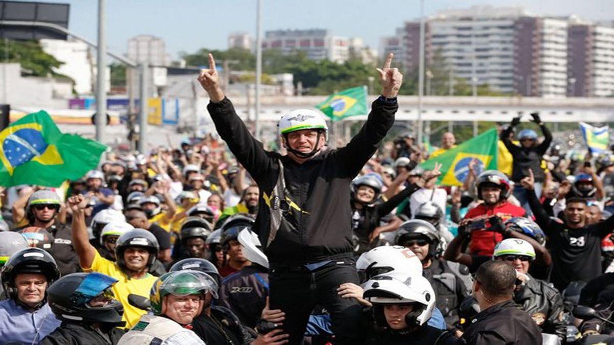 Un grupo de motoristas rodea al presidente brasileño, Jair Bolsonaro, el 23 de mayo, en Río de Janeiro, en una manifestación a su favor, en que destaca que todos están sin mascarillas y sin mantener ninguna distancia de seguridad. (Foto: Alan Santos/PR)