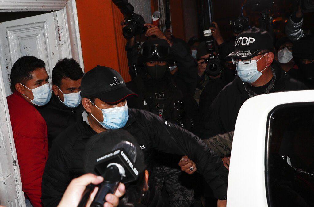 Tras la detención de Jeanine Áñez junto al exministro de Justicia de Bolivia, Álvaro Eduardo Coimbra, y el exministro de Energía, Rodrigo Guzmán, eran escoltados este viernes 12 de marzo de 2021 desde el Instituto de Investigaciones Forenses a un vehículo de la policía, en La Paz, Bolivia. (Foto: fuente AP)